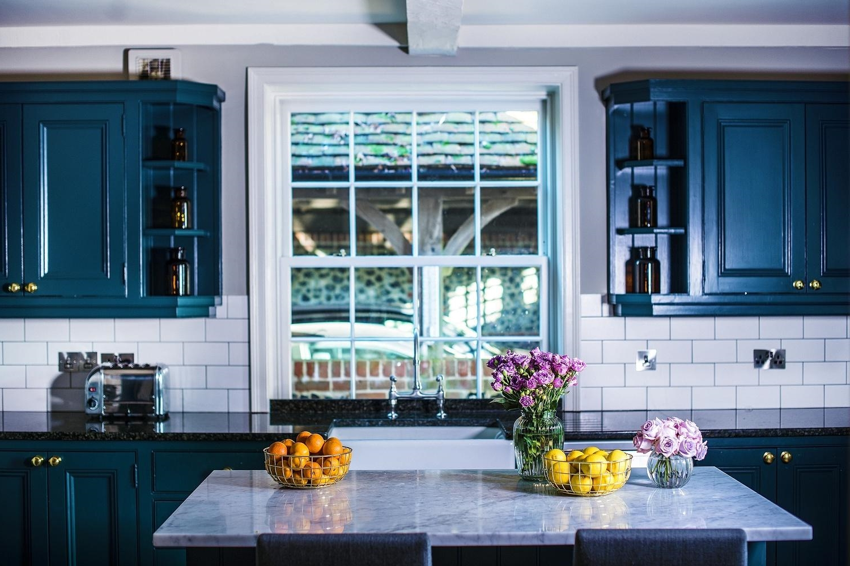 Pour la peinture des armoires, choisissez le bleu de pétrole. Et pour plus de contraste, laissez les carreaux en blanc.