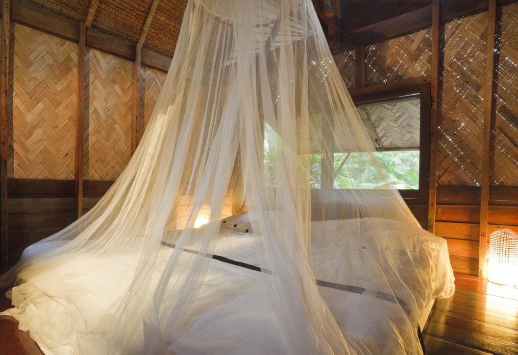 Pour donner un look tropical à votre chambre, combinez du bois et des textiles transparents blancs.