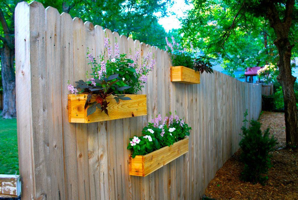 Déco de la clôture de jardin avec des étagères de fleurs