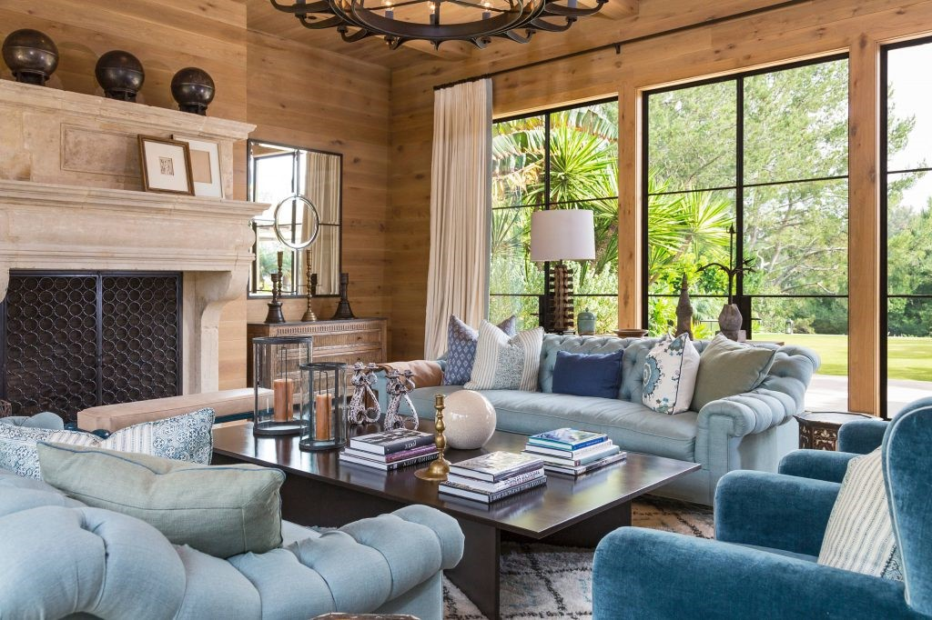 Des murs en panneaux de bois, un tapis moelleux, des sièges confortables et un feu de cheminée, quoi de mieux que de passer l'après-midi à lire dans ce salon cosy?