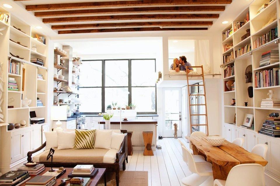 Installez-vous confortablement dans un salon couleur crème avec des éléments naturels comme des accents de bois affichés au plafond et sur la table à manger.