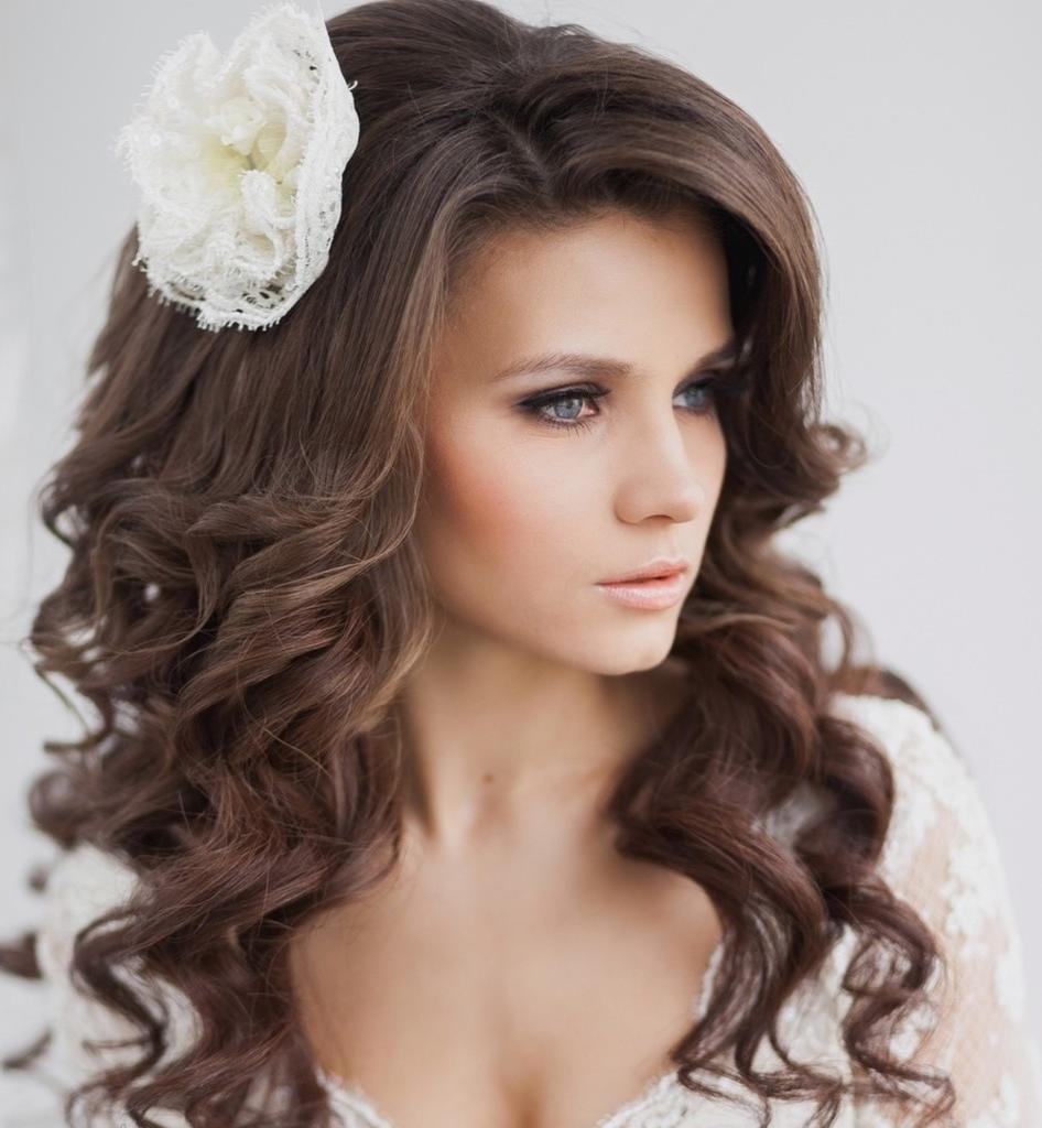 Une coiffure de mariage élégante avec des bouquets et une fleur de cheveux longs