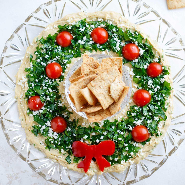 Houmous avec persil et tomates cerises formées dans une belle couronne.