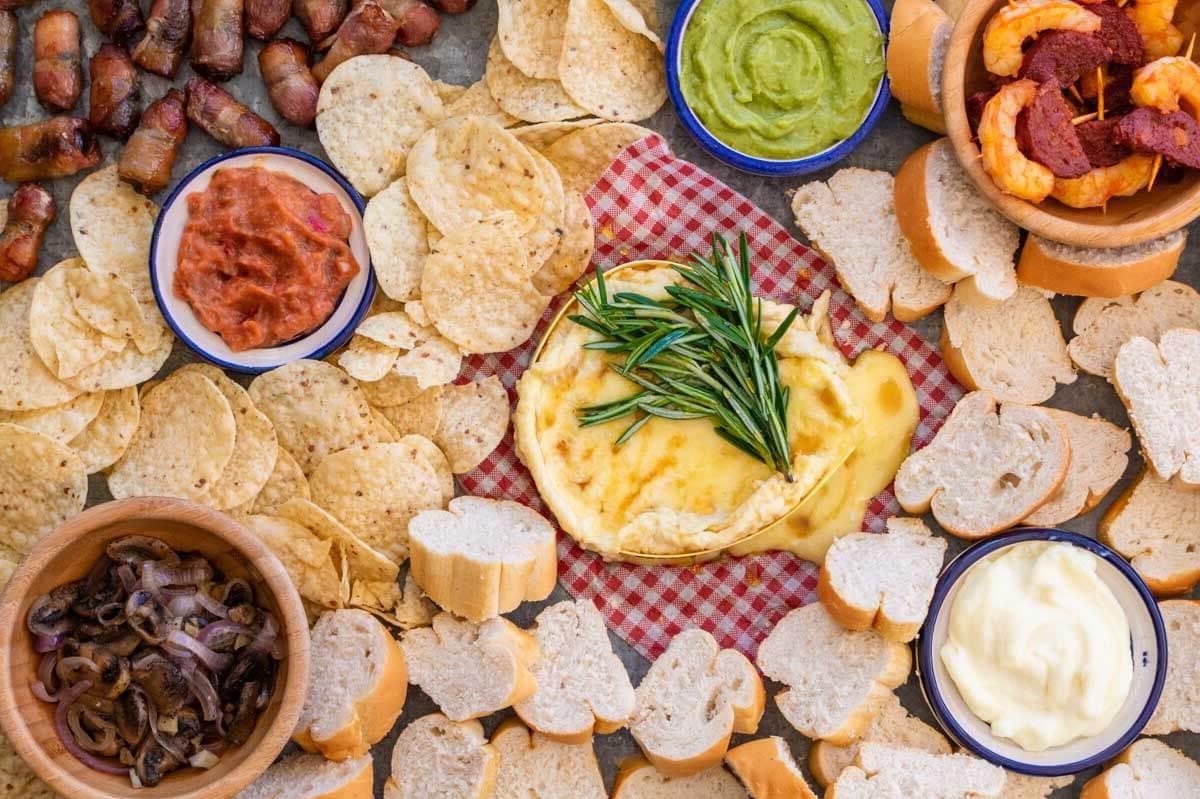 Camembert cuit au four avec garniture de guacamole, pain et chips.