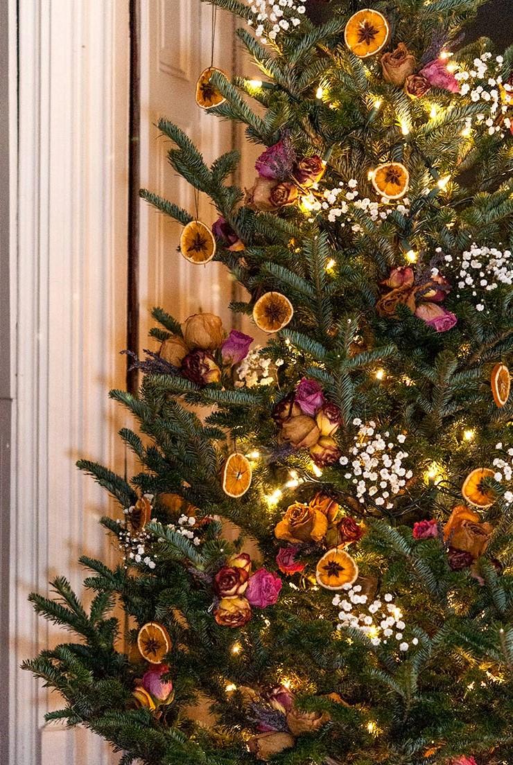 Décoration de Noël naturelle avec des morceaux d'orange séchée et des roses séchées.