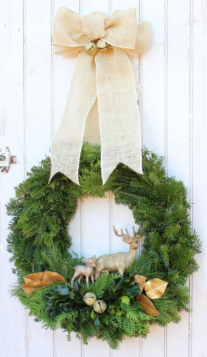 Couronne en feuillage persistant décoré de cerfs en bois.