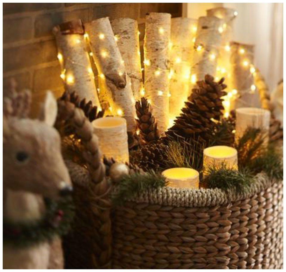 Décoration de Noël naturelle: panier rempli de pommes de pin et de guirlande lumineuse.