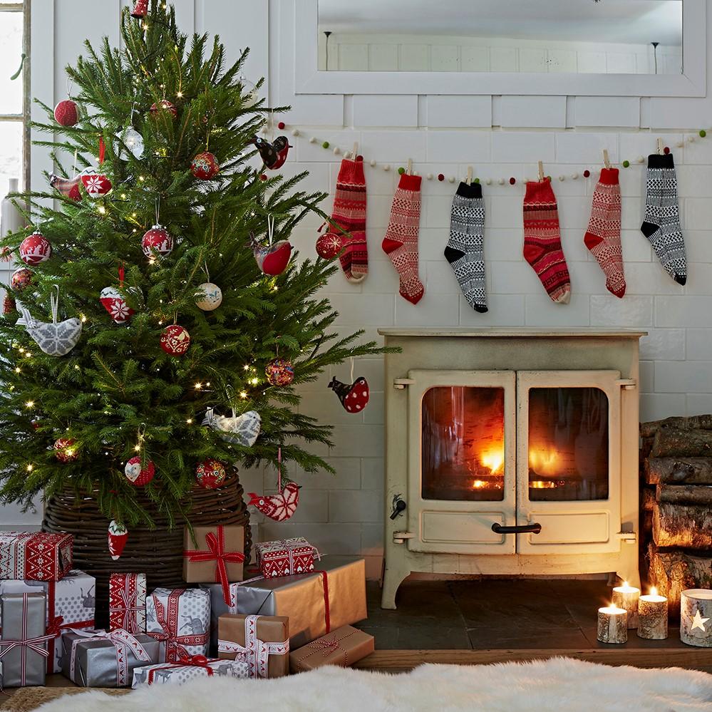 Idées de décoration de Noël: charme rustique avec guirlande de chaussettes au-dessus de la cheminée.