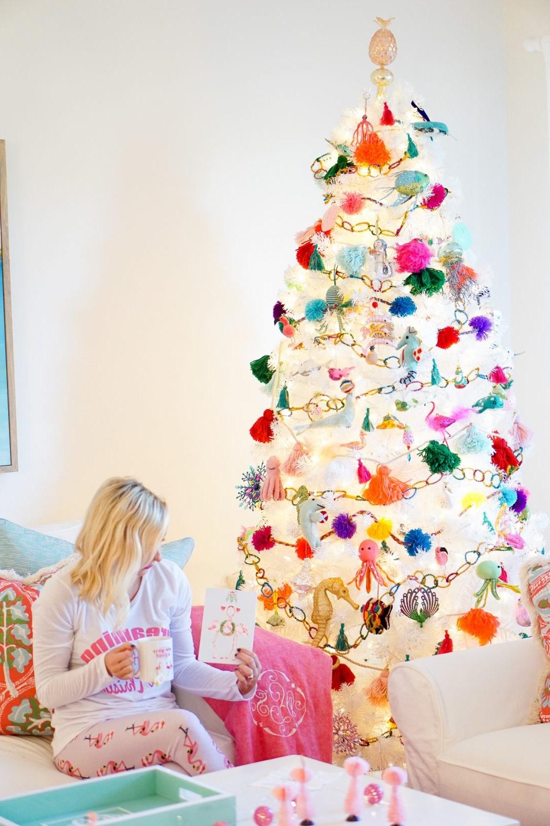 Déco festive: sapin blanc décoré de lumières et d'ornements colorés.