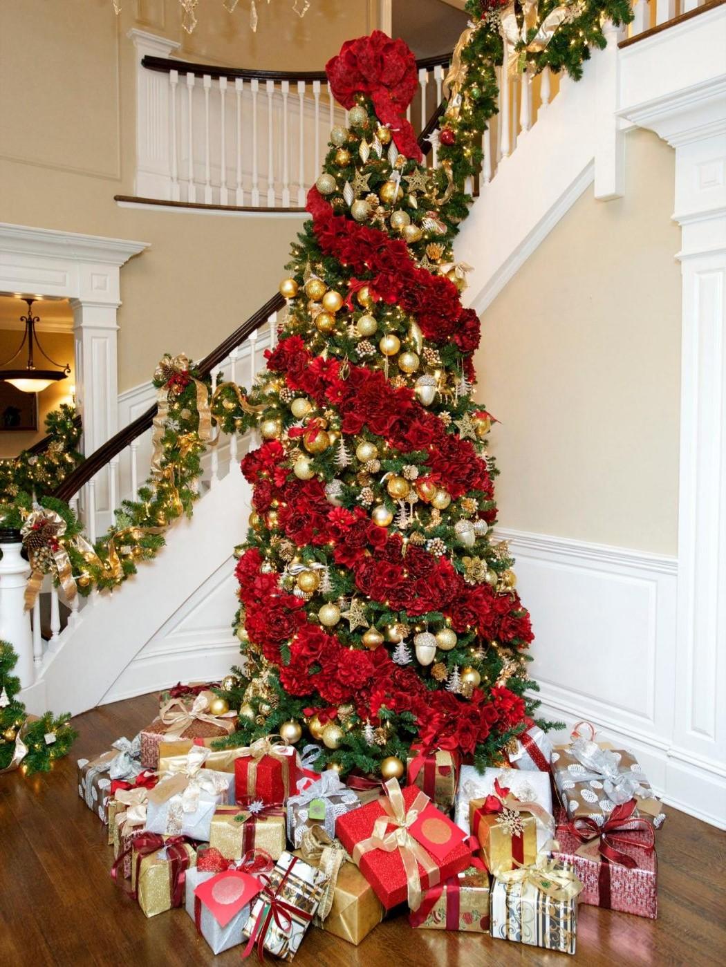 Sapin de Noël décoré d'une guirlande rouge faite de fleurs.