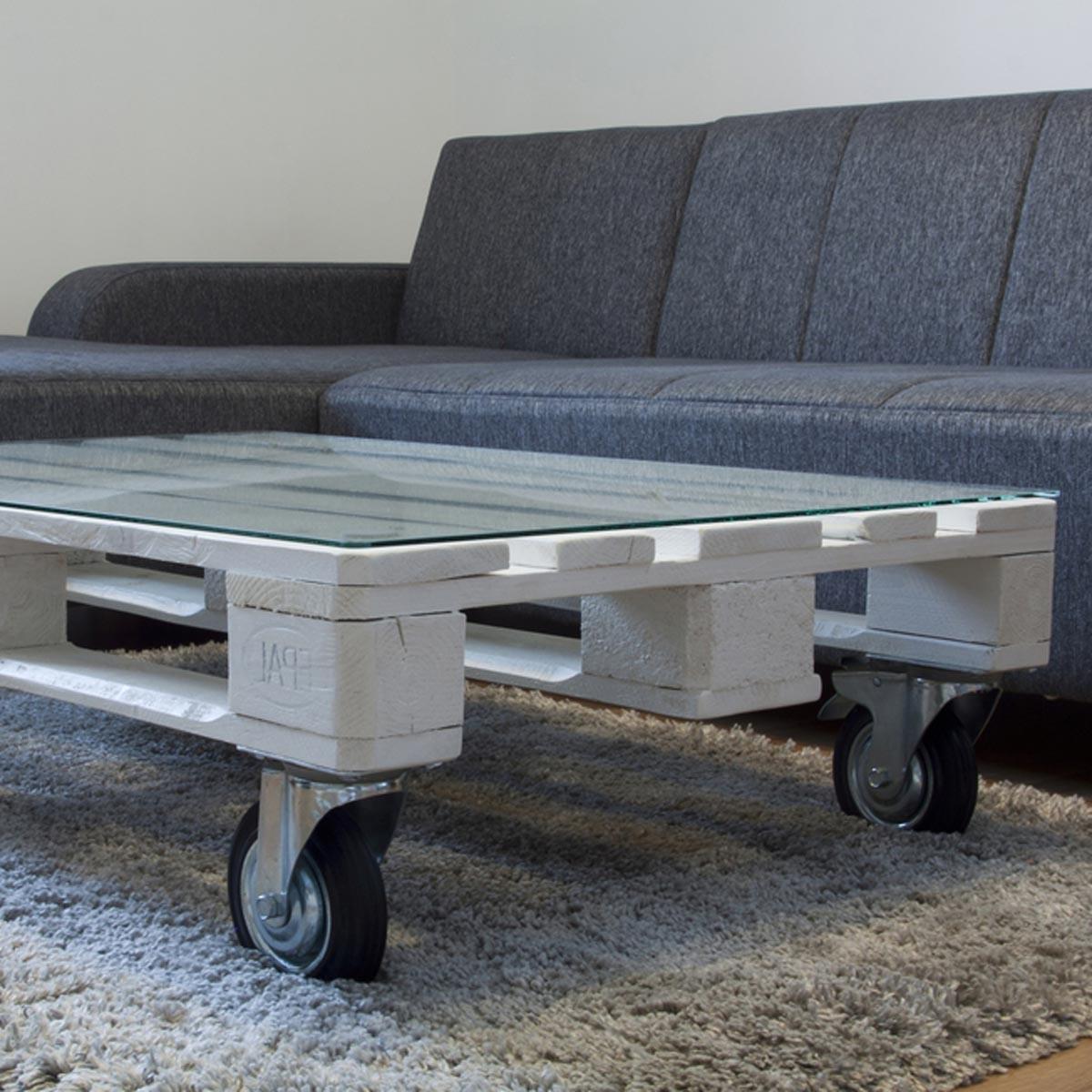 Table basse en palette blanche avec roues pivotantes.