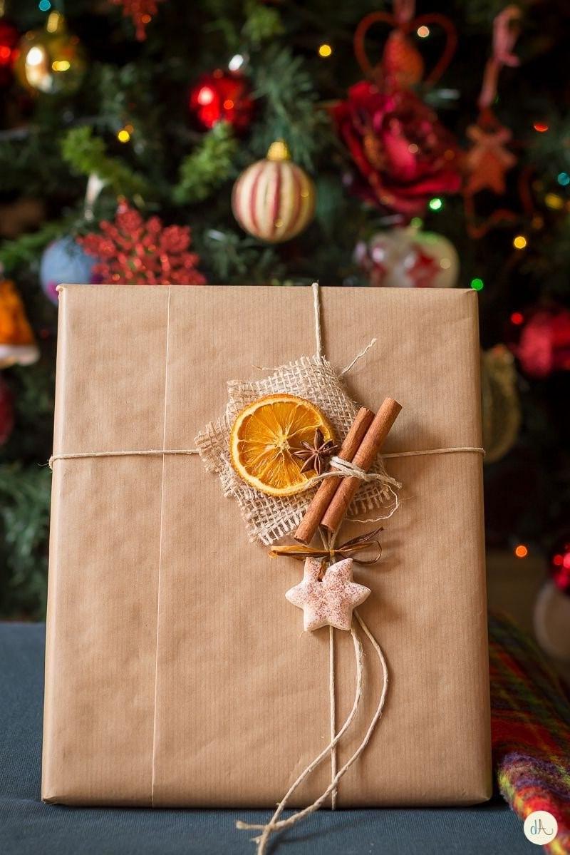 Emballage cadeau avec des bâtons de cannelle et des oranges séchées.