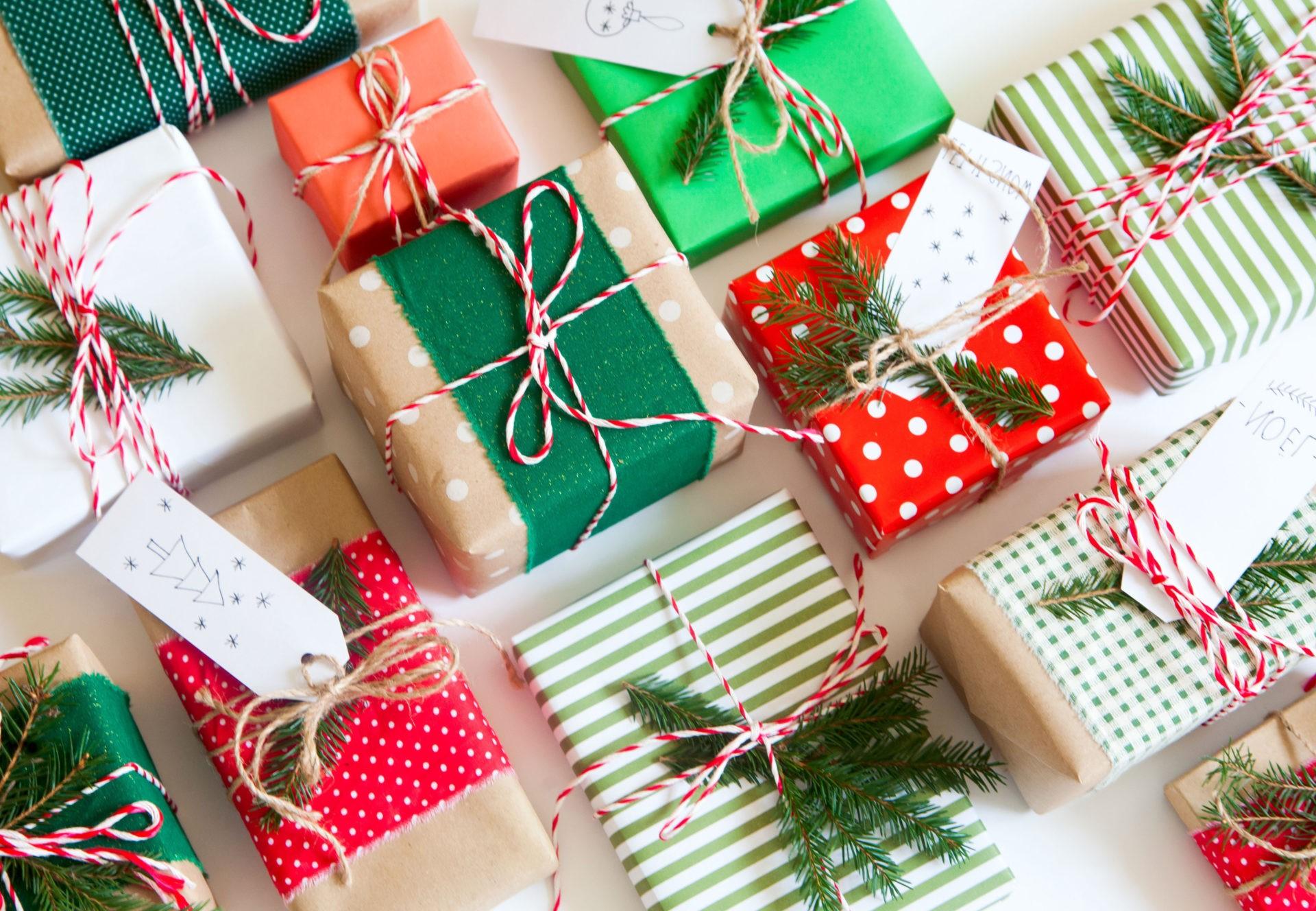 Emballage cadeau rouge, vert et blanc décoré de plantes à feuilles persistantes.