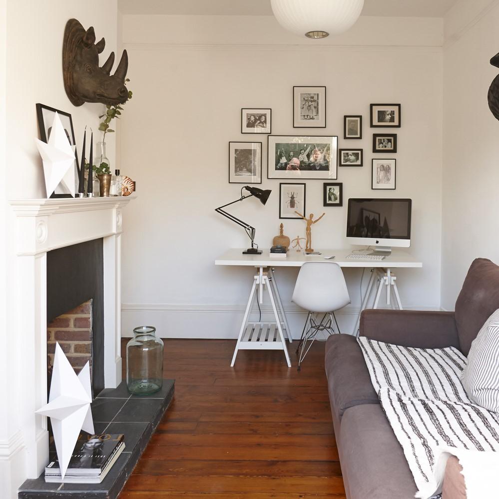 Bureau dans un salon décoré d'une galerie au mur.