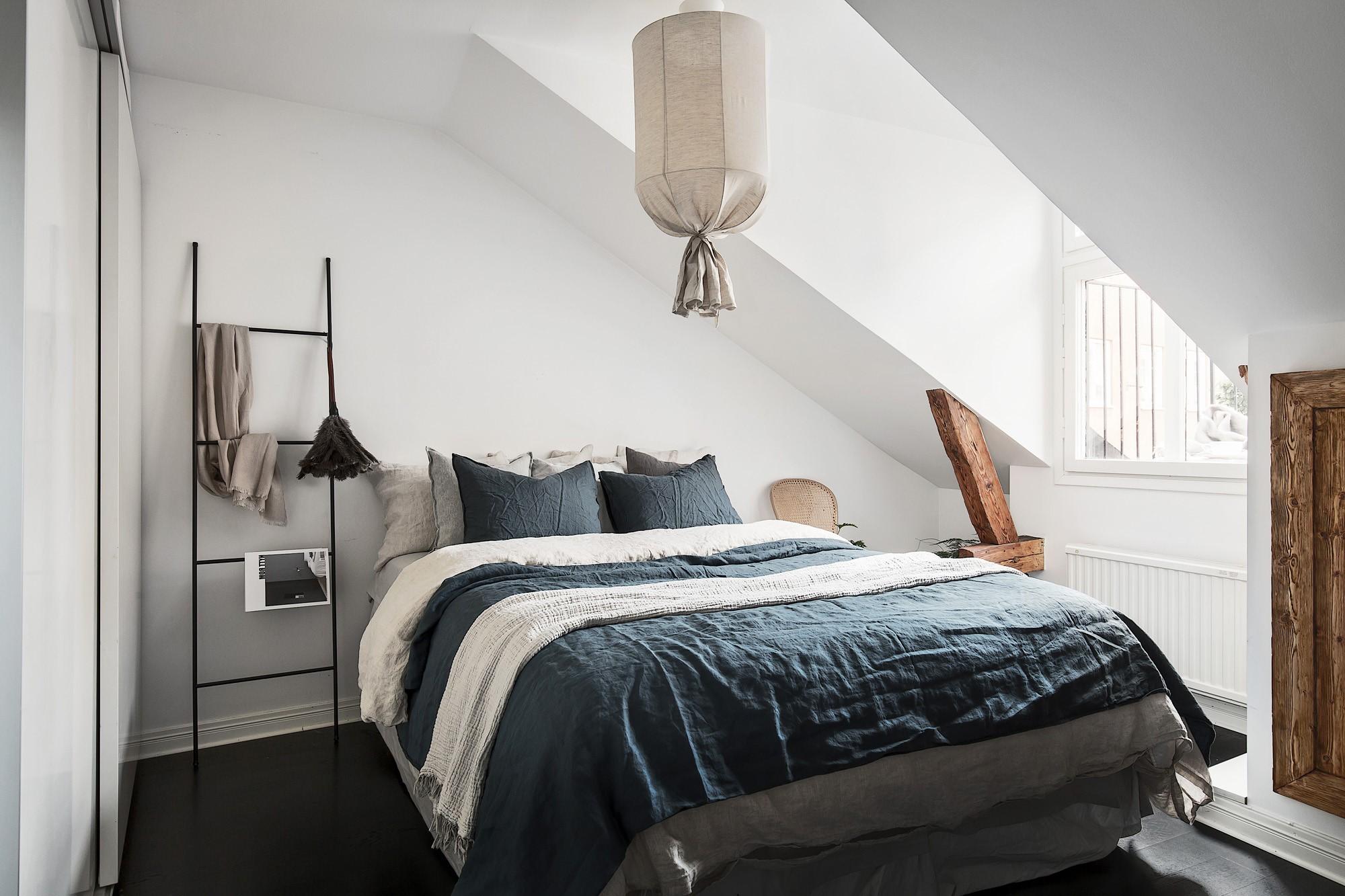 Si vous décidez de transformer votre chambre sous comble en chambre à coucher, profitez-en avec des draps confortables et une lumière suspendue.