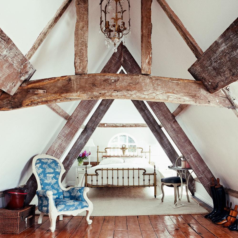 Transformez lachambre sous comble en utilisant un plafond à poutres rustiques et un parquet en bois.