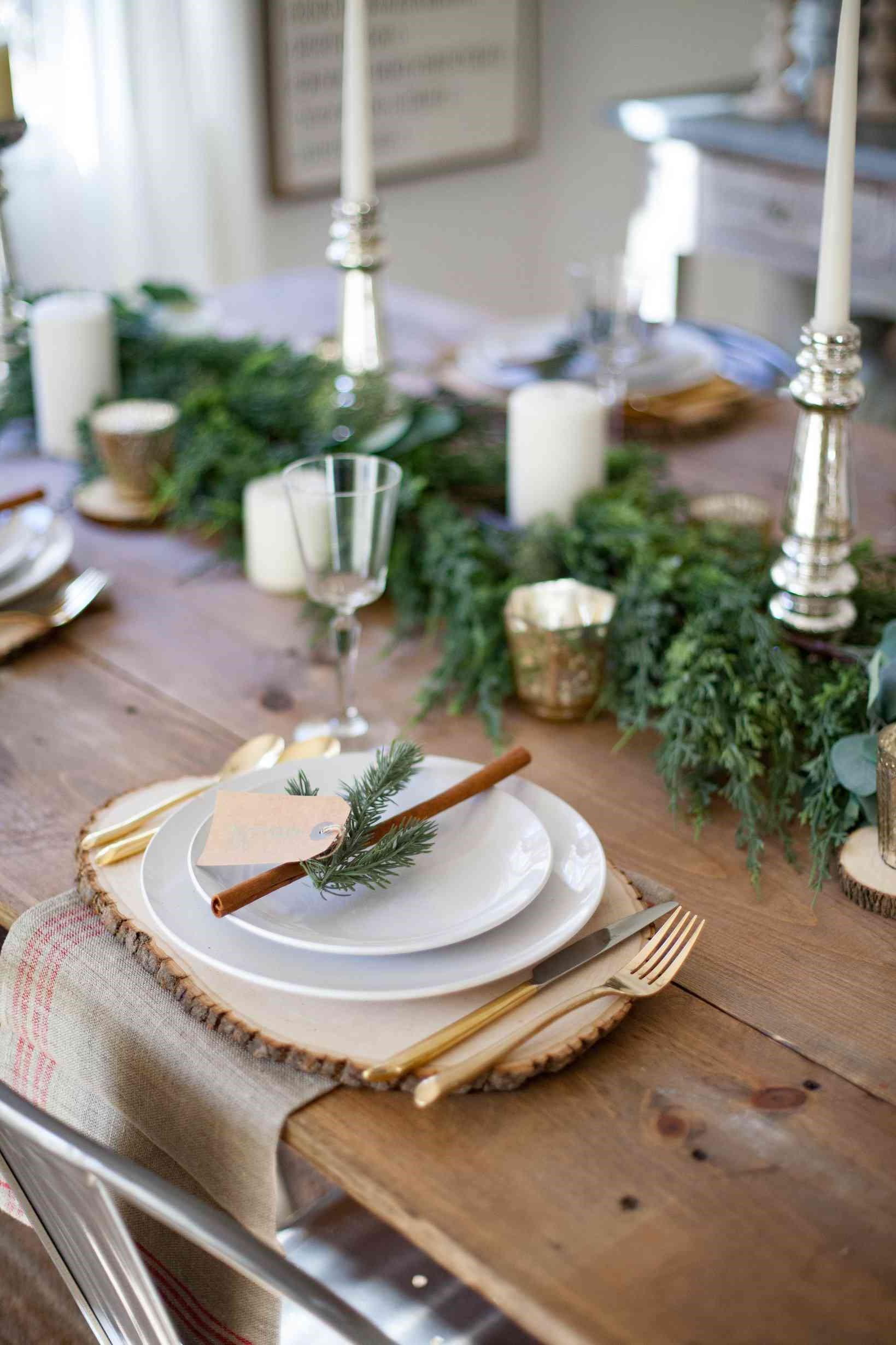 Déco de Noël naturelle avec des plantes à feuilles persistantes et des bâtons de cannelle.