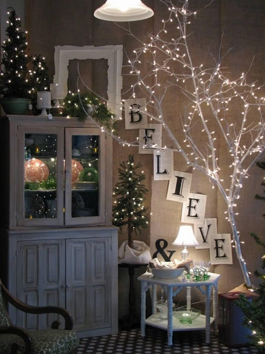 Décorer une branche d'arbre peinte en blanc avec des lumières de Noël est une idée très à la mode.