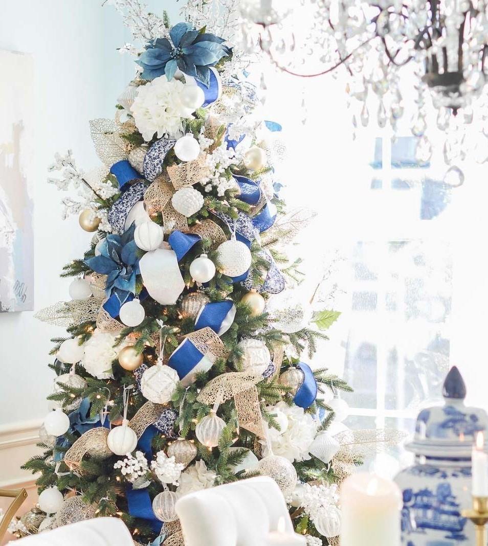 Au lieu d'une étoile, choisissez un poinsettia géant pour le dessus de votre sapin de Noël en blanc et bleu.