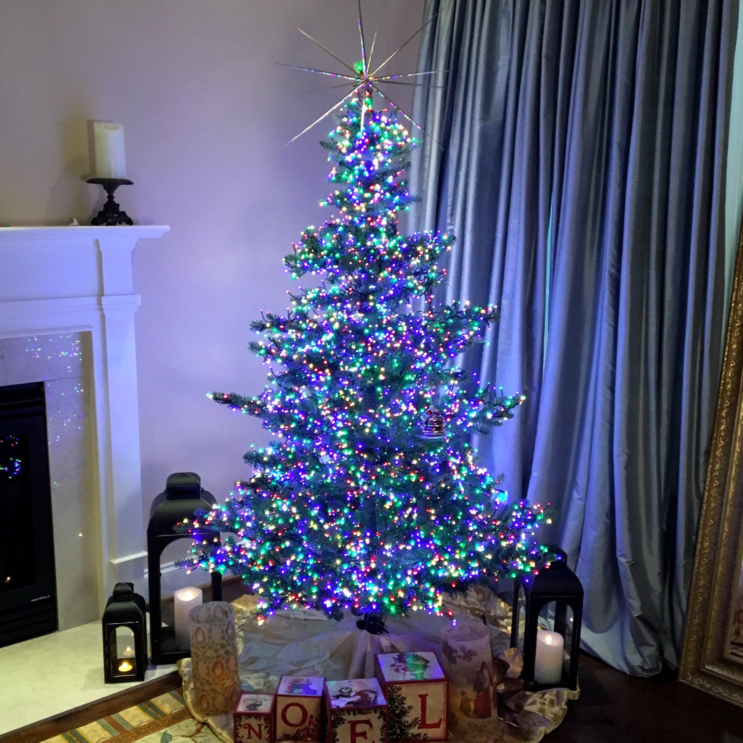 Arbre de Noël avec une décoration en blanc, bleu, vert et violet.