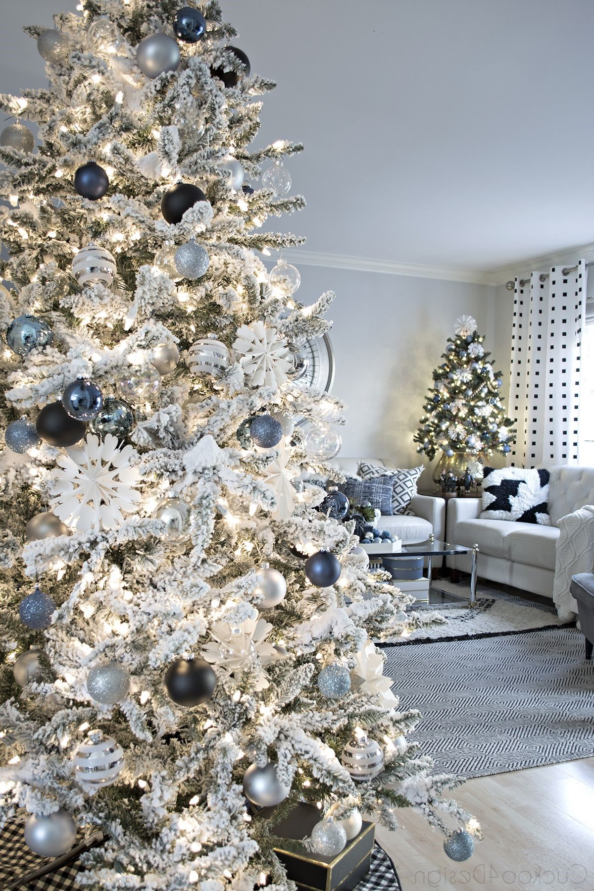 Arbre de Noël en blanc avec des éléments métalliques bleus et gris.