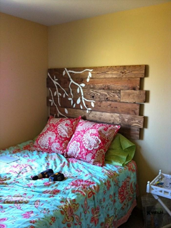 Tête de lit décorée de branches d'arbres blancs.