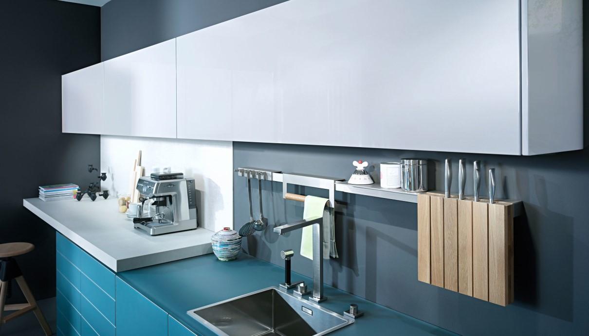 Cuisine moderne avec des armoires bleu canard et comptoirs blancs.