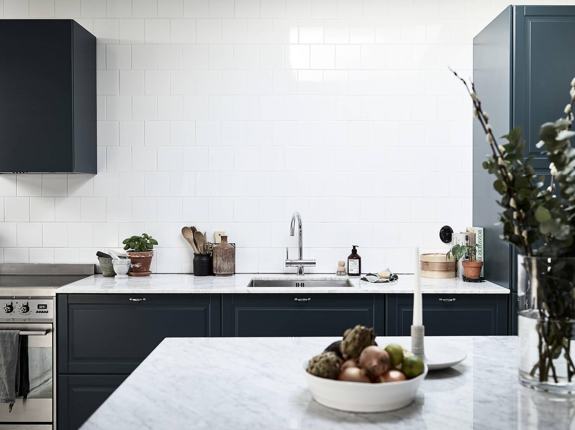 Armoires de cuisine bleu canard avec des comptoirs blancs.