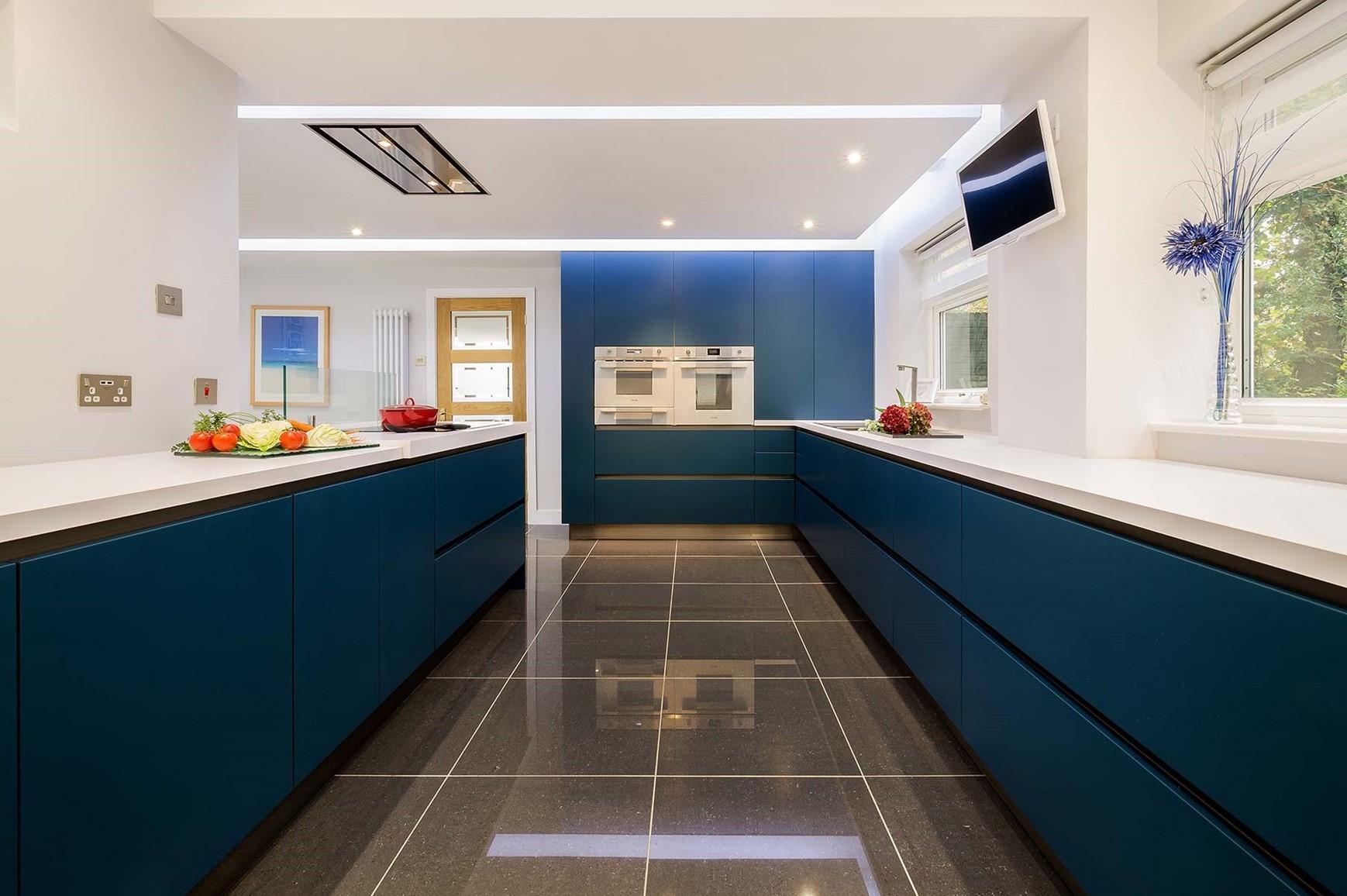 Armoires de cuisine bleu canard en combinaison avec des murs et des comptoirs blancs.