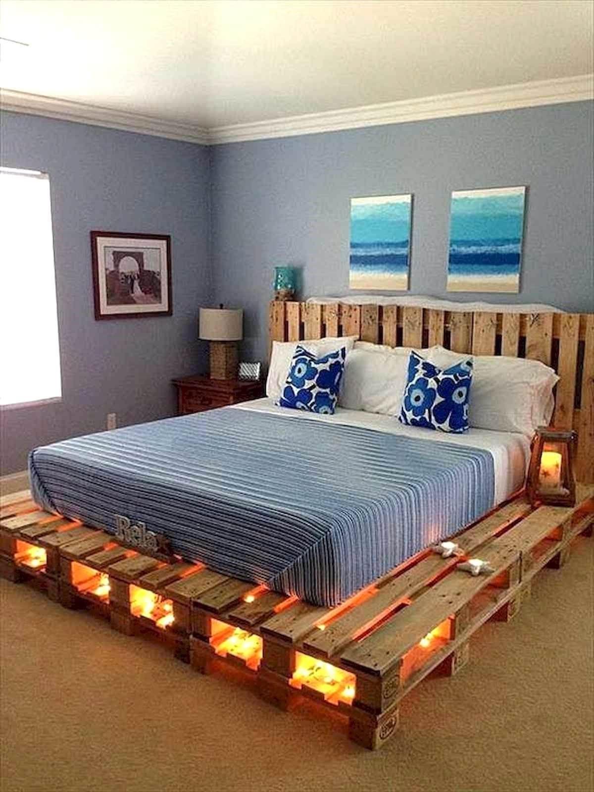 Cadre de lit en palette décoré avec des guirlandes lumineuses.
