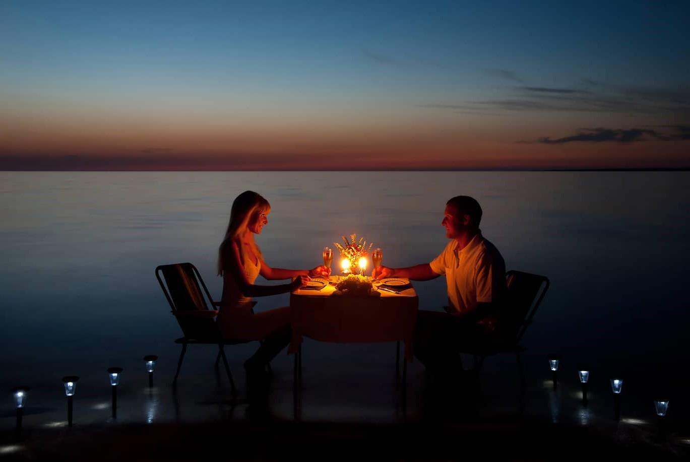 Dîner romantique avec des bougies au bord de la mer.