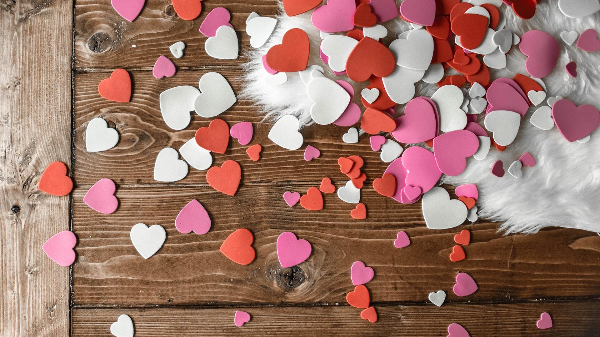 Couvrez le lit de confettis en forme de cœur.