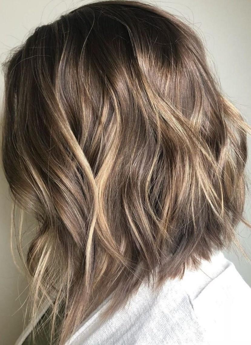 Cheveux mi-longs ondulés.