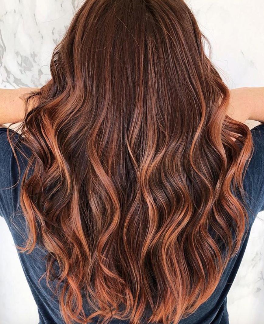 Cheveux ondulés avec des mèches couleur miel.