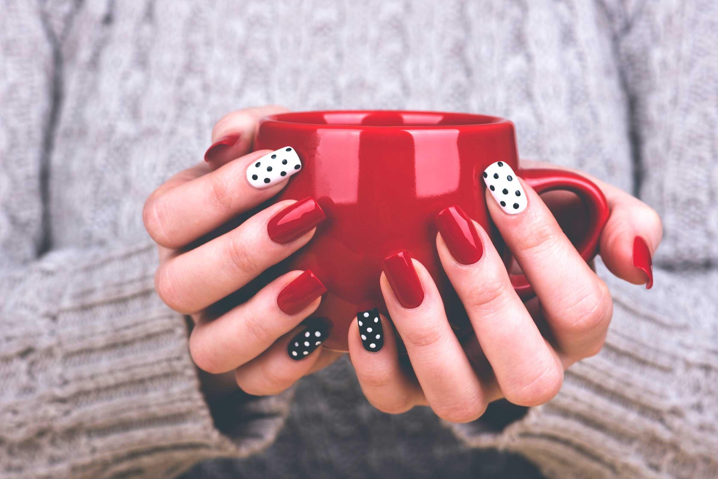 Manucure en rouge, noir et blanc.