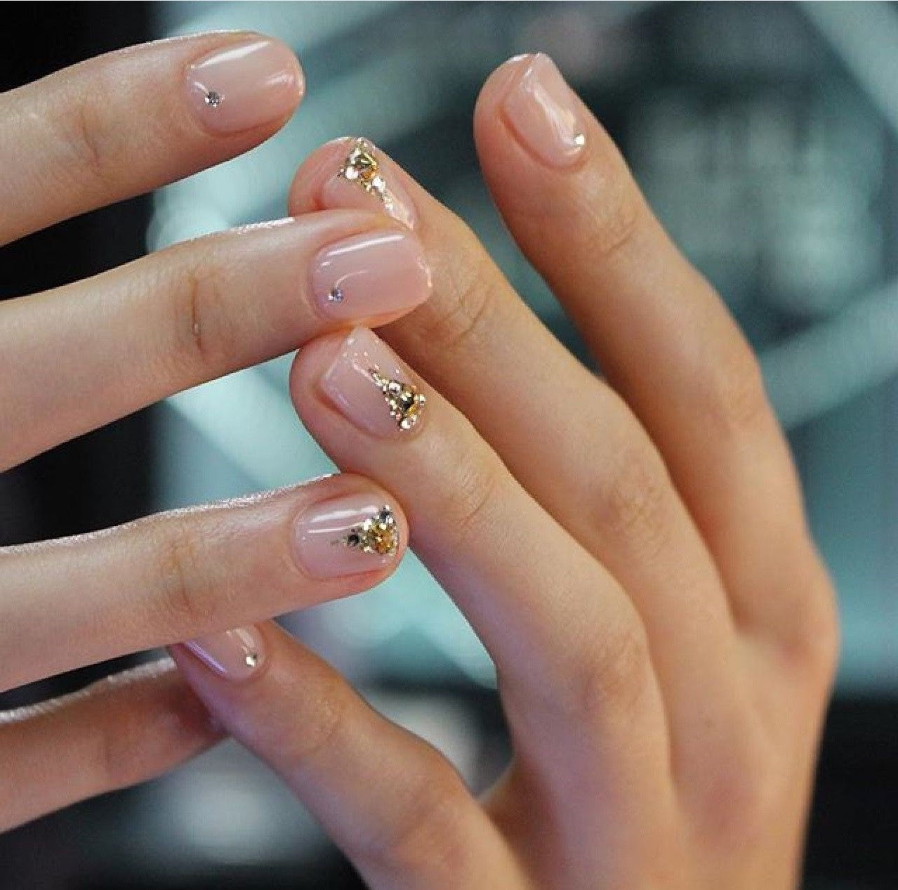 Vernis à ongles nude avec des éléments dorés.