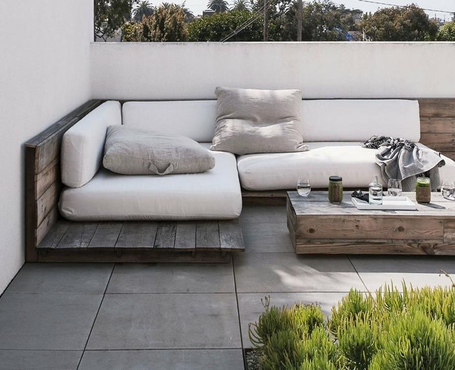 Décoration de terrasse élégante avec des meubles en palette et des textiles blancs