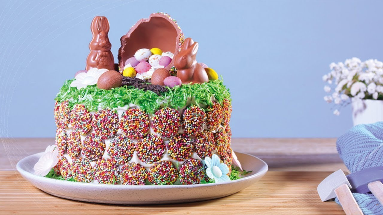 Gâteau de Pâques décoré de lapins au chocolat et d'oeufs multicolores.
