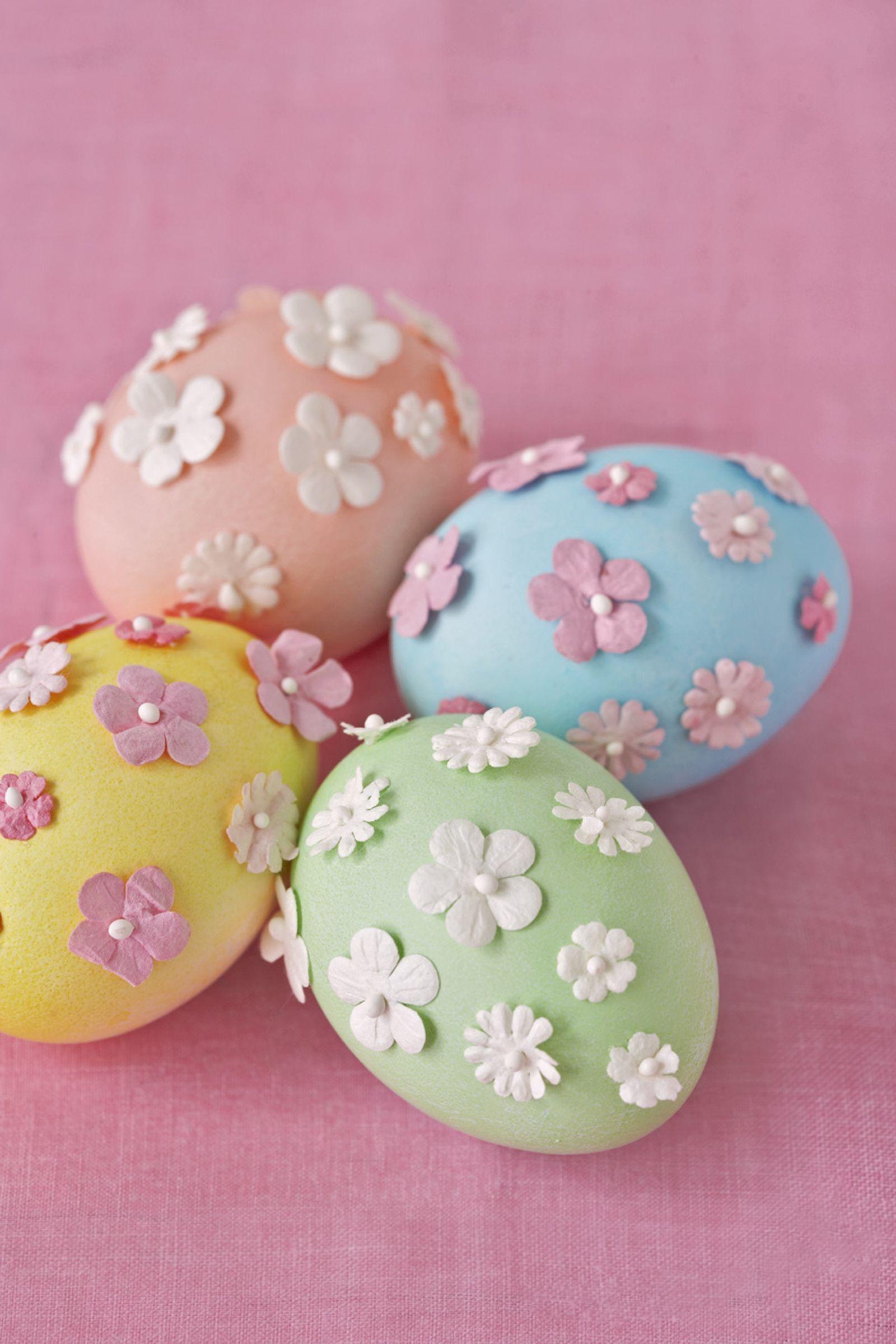 Oeufs de couleur pastel ornés de mini fleurs en papier.