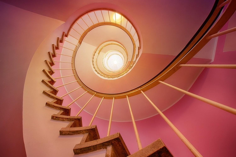 Escalier en colimaçon orné de papier peint rose.