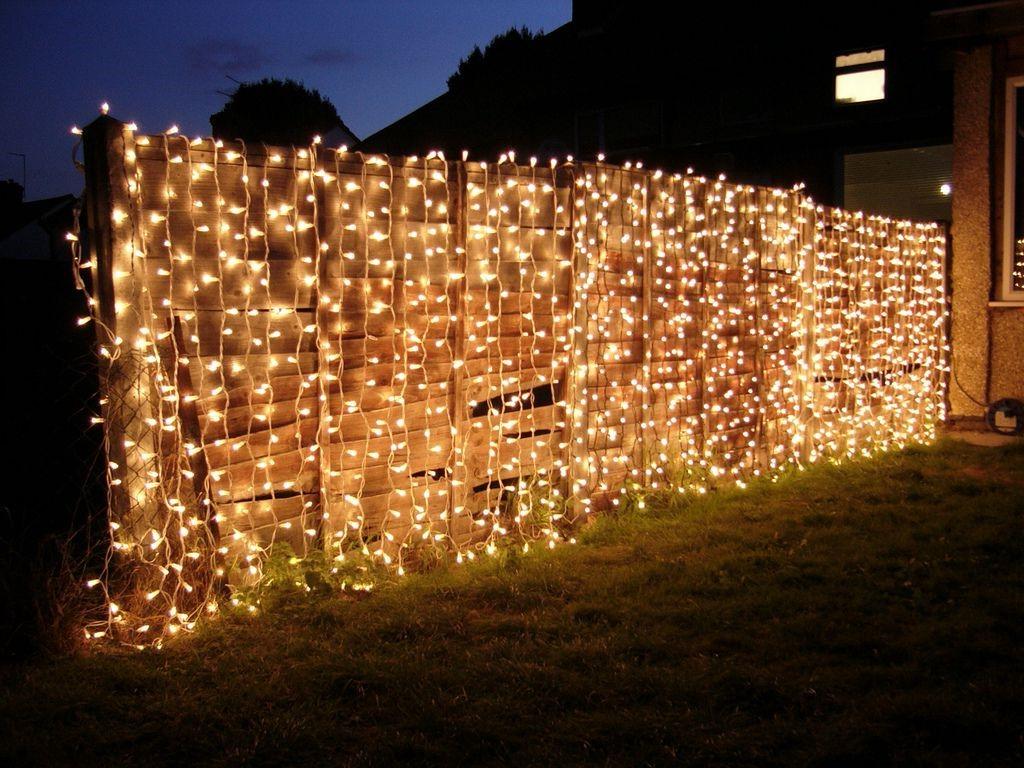 Clôture en bois illuminée avec plusieurs guirlandes lumineuses.