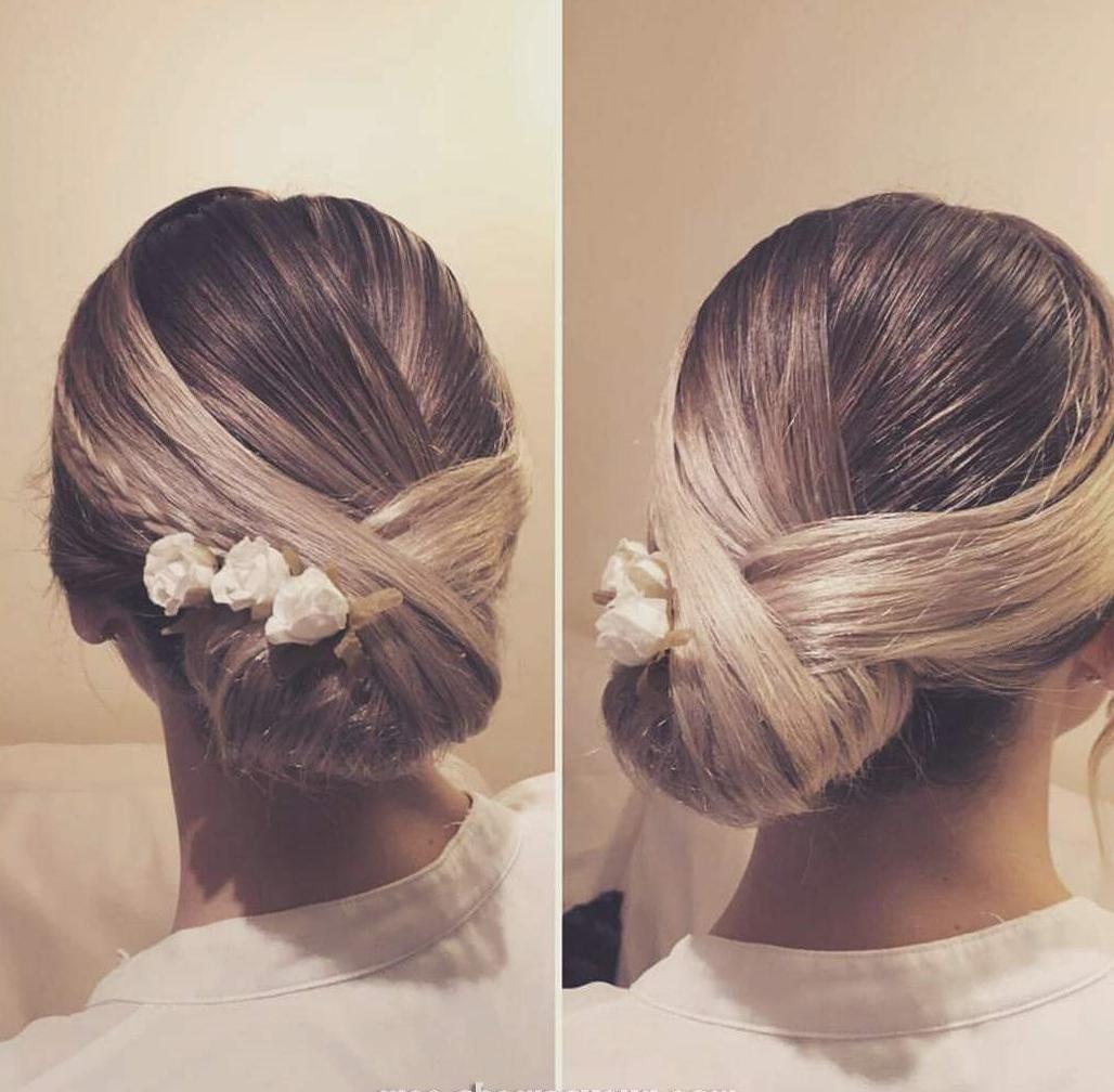 Coiffure attachée - chignon bas avec des fleurs