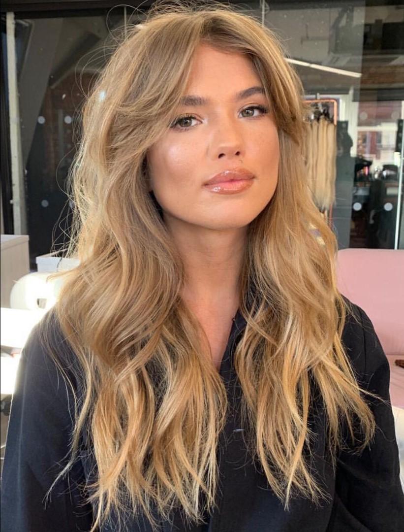 Deux tendances en une: cheveux ondulés avec une frange rideau.