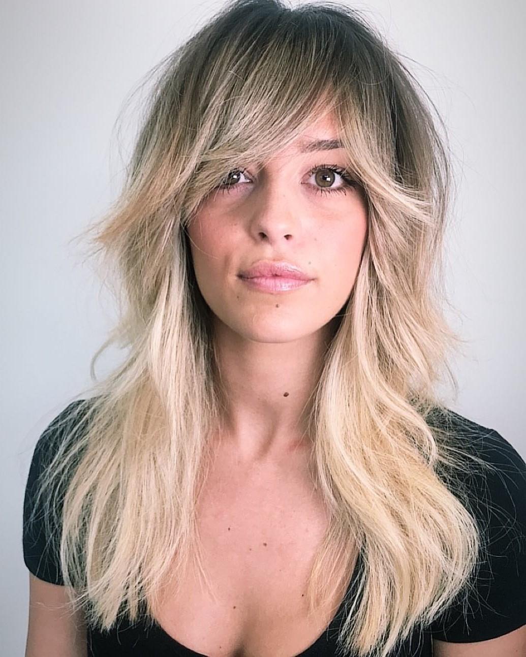 Balayage blond sur cheveux longs dégradés.