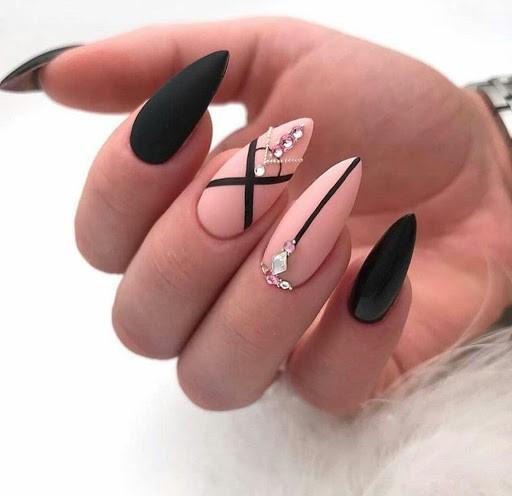 Nail art rose et noir décoré de pierres précieuses.