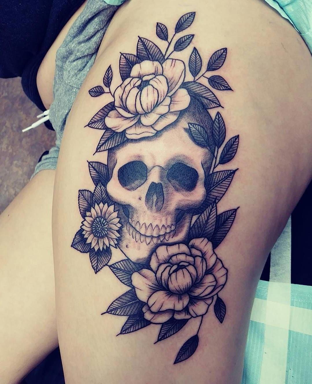 Tatouage sur cuisse pour femme avec un crâne.