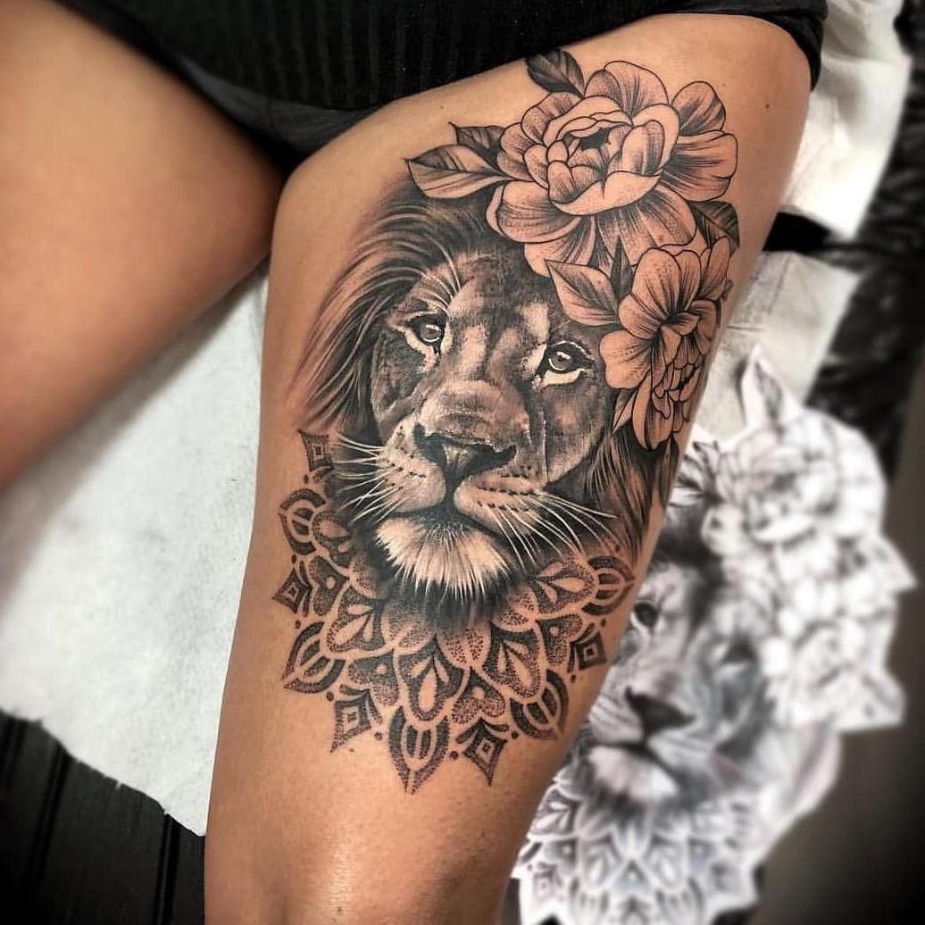 Tatouage sur la cuisse pour femme: lion réaliste avec une couronne de fleurs.