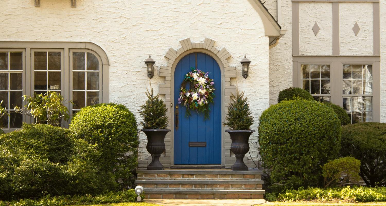Aménagement de porte d'entrée avec des plantes à feuilles persistantes.