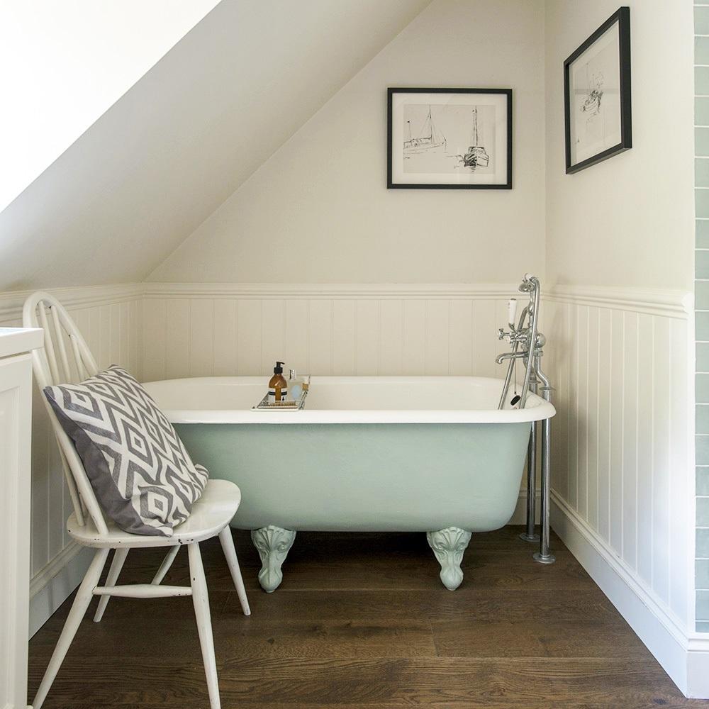 Salle d'eau sous pente avec baignoire couleur pastel.