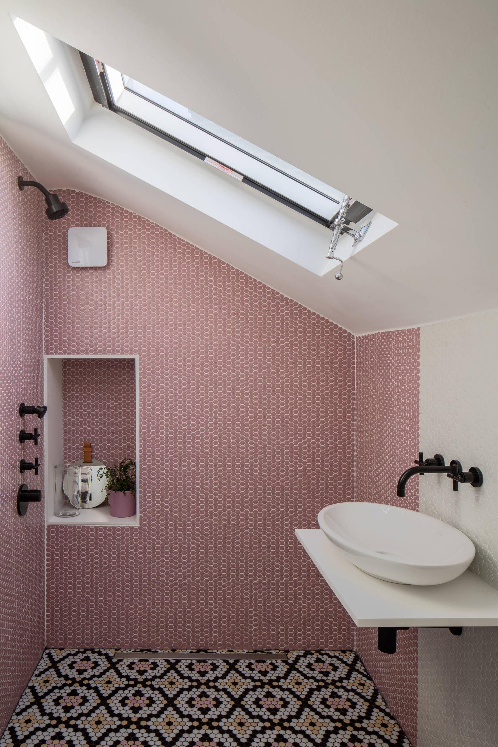 Salle d'eau sous combles avec des carreaux couleur rose.
